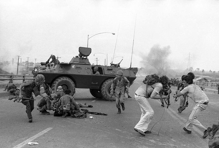 Quân lính Nam Việt Nam và nhóm phóng viên truyền hình Phương Tây tìm chỗ trú ẩn trước đạn pháo của người Bắc Việt ở cầu Tân Cảng, Sài Gòn, 28 tháng Tư 1975. Hình AP Photo Hoanh.
